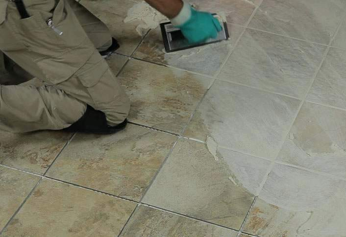 Foto de homem aplicando rejunte no piso