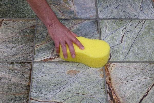 Foto de uma pessoa limpando rejunte com esponja