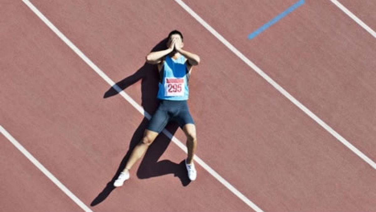 Homem deitado na pista de atletismo com as mãos na cara