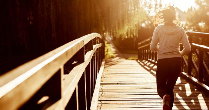 Mulher correndo ao por do sol.