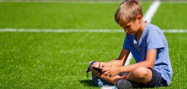 Menino vendo o celular sentado em um campo de futebol